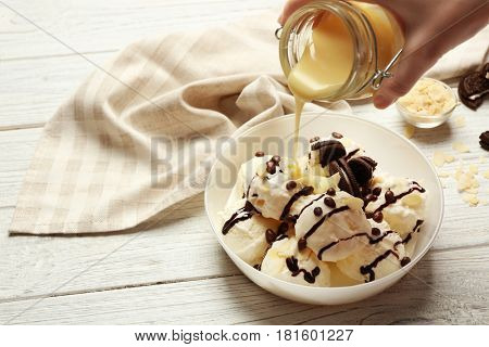 Pouring sauce onto delicious dessert with ice cream in bowl