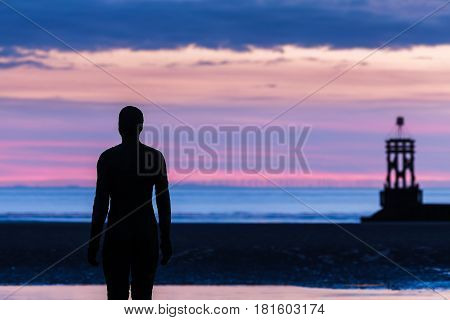 The warm colours of the sunset make way for the cooler colours of twilight at Crosby beach near Liverpool - home to 100 cast iron statues created by Antony Gormley.