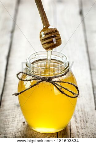Honey jar with dipper and flowing honey on a wooden background and