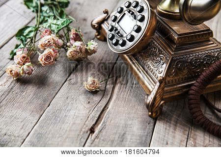 Old vintage black rotary phone and a bouquet of roses on wooden background and