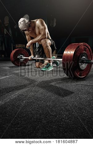 man cross strongman training - heavy deadlift workout with big dumbbell