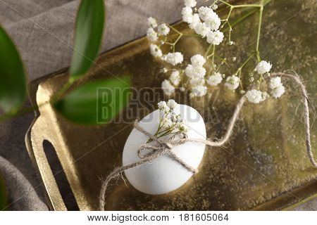 Easter egg decorated with flowers and branch on golden tray