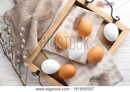 Wooden tray with Easter eggs and napkin on white table