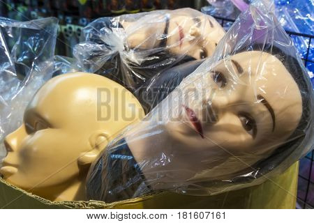 Mannequin shop dummy heads in plastic bags waiting for display