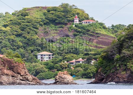 Houses occupy the slopes of Guanacaste as waves crash against the rocky coast.