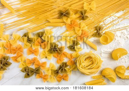 An overhead photo of various types of pasta on a white marble table with flour