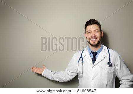 Handsome doctor standing on light background