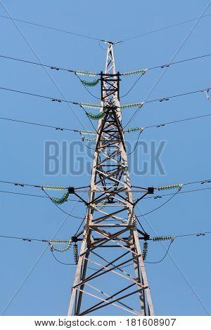 Power transmission tower. High voltage. Wires. Insulators. Blue background. Vertical shot.