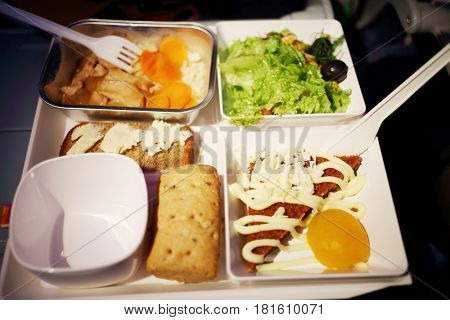Lunch in an airplane with salad, hot mushrooms, sandwiches and cake