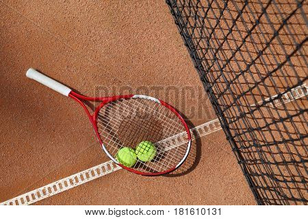 Tennis racket and two balls near net on court at sunny summer day