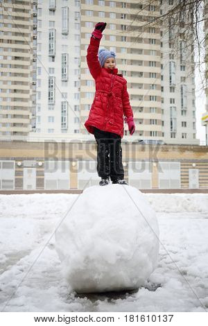 Happy girl in red raises arm on large snowball near buidling at winter day