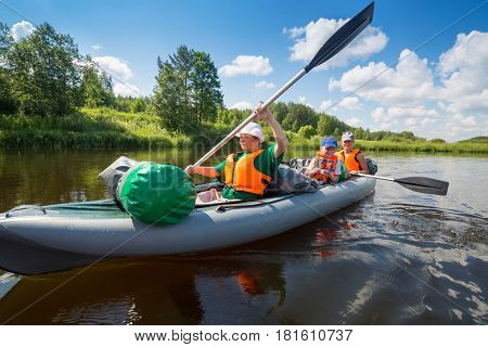 Two women with oars and little boy sail on inflatable boats on river at sunny summer day