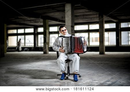 The musician playing the harmonica, accordion in the hall with columns, Factory premises