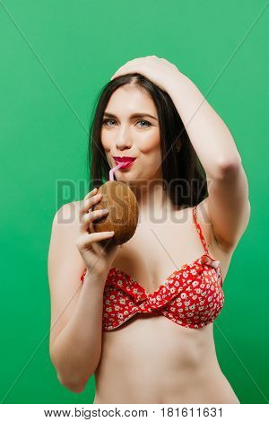 Portrait of Joyous Female Model in Bright Swimsuit Drinking Tropical Cocktail on Green Background in Studio. Pretty Dark-haired Girl with Beverage in Coconut in Hand. Isolated. Summer Holiday Concept.