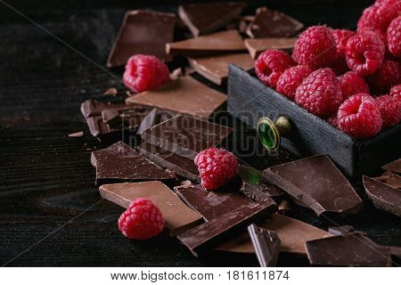 Dark and milk chopping chocolate and chips shavings chopping chocolate with fresh raspberries in black wood box over black burnt wooden background. Close up. Chocolate dessert concept