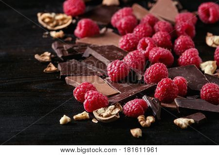 Dark and milk chopping chocolate and chips shavings chopping chocolate with fresh raspberries heap and cracks walnuts over black burnt wooden background. Close up. Chocolate dessert concept