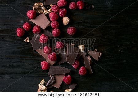 Dark and milk chopping chocolate and chips shavings chopping chocolate with fresh raspberries heap and cracks walnuts over black burnt wooden background. Top view with space. Chocolate dessert concept