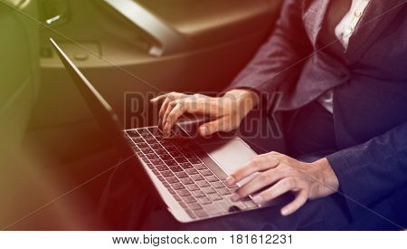 Businessman using laptop on backseat of the car