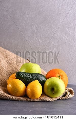 Various Fruits: Lemon, Apple, Orange, Avocado On Sackcloth Napkin