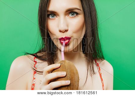 Closeup Portrait of Joyous Female Model Drinking Cocktail in Coconut on Green Background in Studio. Summer Holiday Concept.