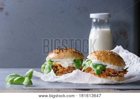Homemade mini burgers with pulled chicken, basil, mozzarella cheese and yogurt sauce on baking paper and bottle of milk over gray texture background. Healthy fast food concept