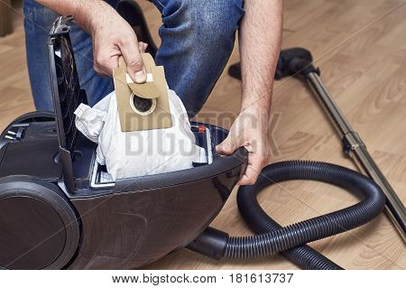 Removing a full dust bag from a vacuum cleaner