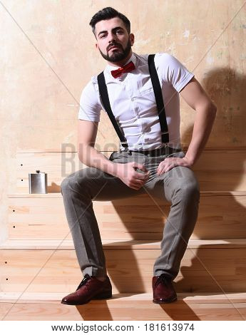 bearded man long beard brutal caucasian hipster with moustache in white shirt and suspenders with bow-tie sitting on wooden stairs with flask with serious face on studio wall background
