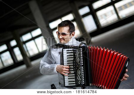 The musician playing the harmonica, accordion in the hall with columns
