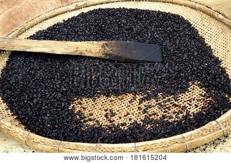 Portion of roasted coffee artisan placed in a sieve to be cleaned