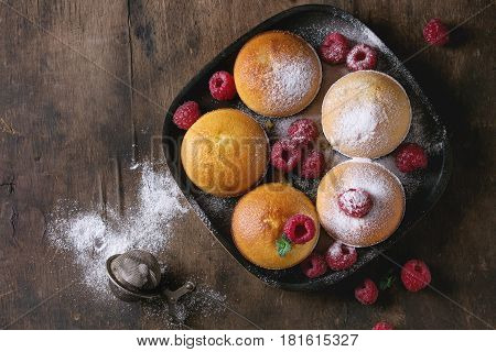Homemade lemon muffin cupcakes with fresh raspberries, sugar powder, mint, served in square wood plate with vintage sieve over old dark wooden background. Top view with space
