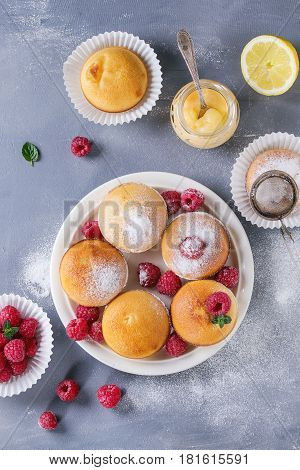 Homemade lemon muffin cupcakes with fresh raspberries, sugar powder, mint, served with jar of lemon curd and lemons over gray blue texture stone background. Top view with space.
