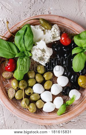Mediterranean appetizer antipasti plate with green black olives, feta cheese, mozzarella, capers, pepper, basil over beige concrete texture background. Top view with space, close up