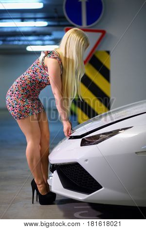 MOSCOW - MAY 20, 2016: Pretty girl opens hood of Lamborghini Huracan LP 610-4. Lamborghini Huracan is world first production car, using inertial navigation system