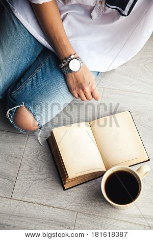 Young modern girl in torn jeans reading a book with a big cup of coffee. Fashion, lifestyle, lifestyle, recreation, education, hobbies. and
