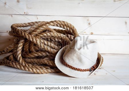 rope and women's straw hat in cowboy style on the wooden background and