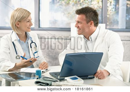 Two medical doctors consulting, smiling at office desk.?