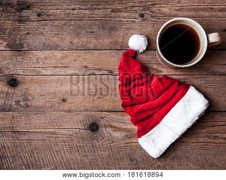 Cup of coffee and Santas hat on a wooden background, celebration and