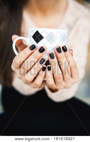 girl hands holding a cup of coffee with beautiful black manicure. Christmas and