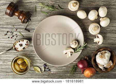 Mushrooms champignons with fresh ingredients on wooden background