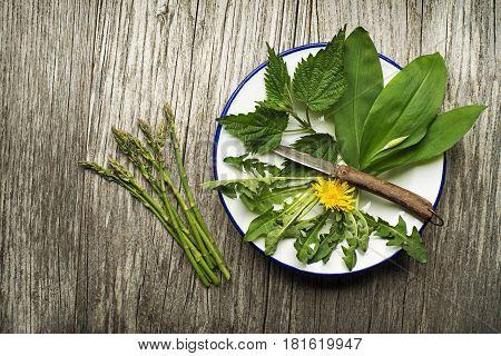 Spring food nettle dandelion wild garlic and asparagus on wooden background