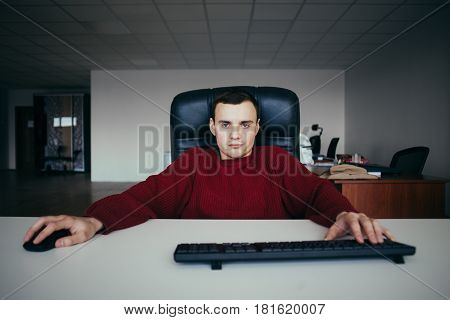Young handsome hipster man running the office at the computer.