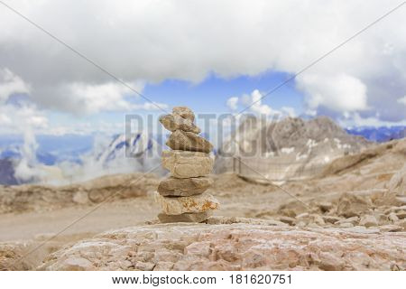 One stone tower in mountains height show balance stability power. Stones stack in mountain panorama with blue sky visualizes creativity consulting success or showing health meditation and therapy.