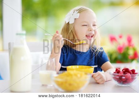Cute Little Girl Enjoying Her Breakfast At Home. Pretty Child Eating Corn Flakes And Raspberries And