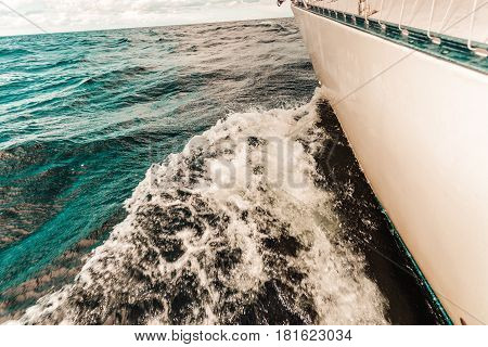 Yachting on sail boat bow stern shot splashing sea water. Sporty transportation conept.