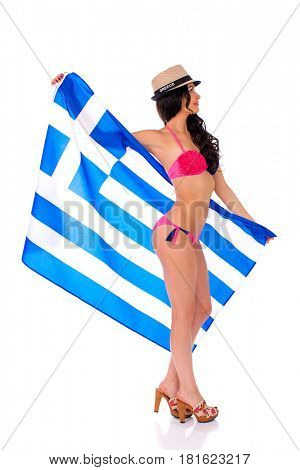 Young beautiful brunette woman in bikini and bonnet holding a large flag of Greece, isolated on white background