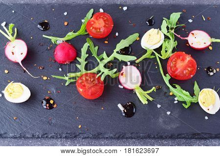 Mixed vegetable salad with radish, quail eggs, arugula and cherry tomatoes with a balsamic glaze