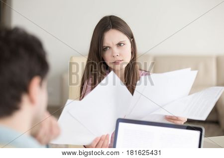Couple discussing domestic bills, bank statements, woman holding papers looking angry and frustrated, found error in incorrect documents, contracts, dissatisfied female client talking with manager