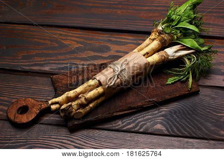 Raw Horseradish Roots On Wooden On Cutting Board Background. Horseradish With Leaves.homemade Wassab