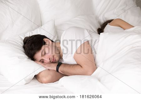 Young guy and lady asleep together, having good dreams, healthy sleep, couple in bed taking a nap back to back. Sleeping man wearing smart wristband tracker for sleep tracking and getting up on time poster