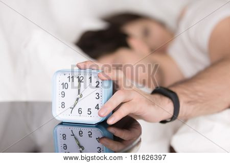 Young couple awaking after wake-up signal in the morning at home. Sleepy man stretching hand to alarm clock touching button to snooze or turn it off. Focus on hand with clock. Time to wake up